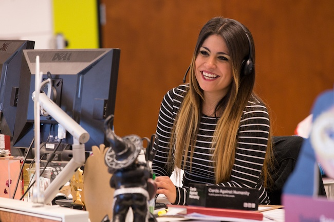 A young woman at work smiling at her desk