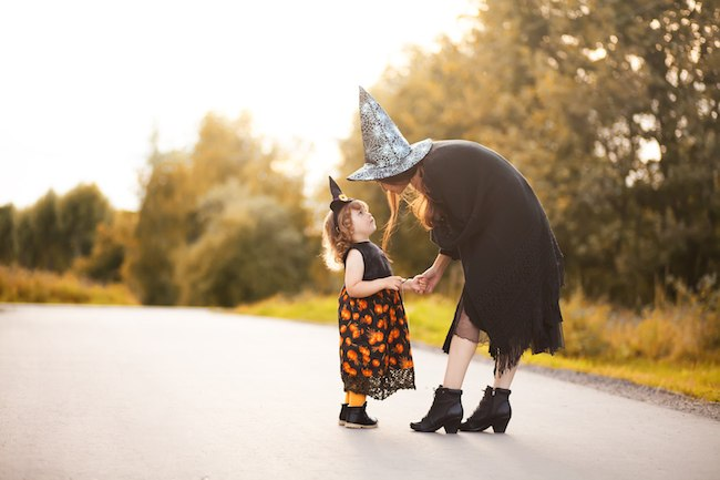 Mother and daughter trick or treating on Halloween