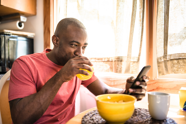 Man, on his phone, eating breakfast at home