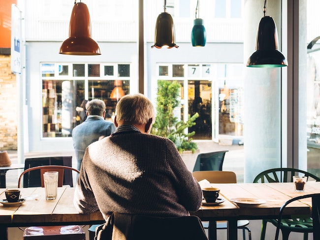 Older man sitting at a coffee shop