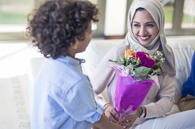 Boy handing his mother flowers