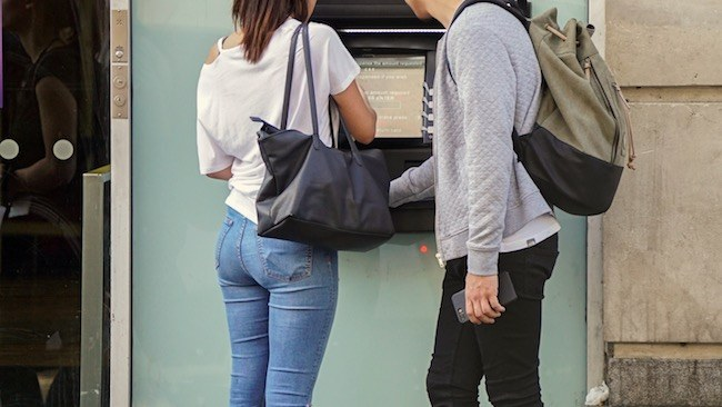 Couple getting money from an ATM
