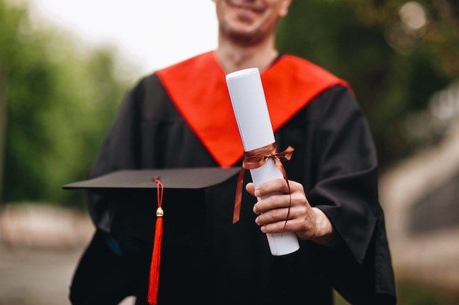 College student holding diploma