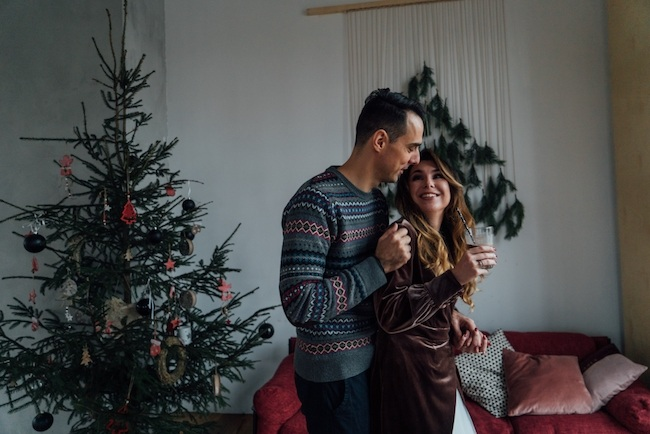 Couple standing by Christmas tree