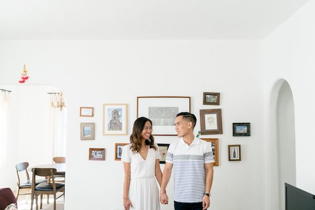 Couple posing in front of a wall in a home