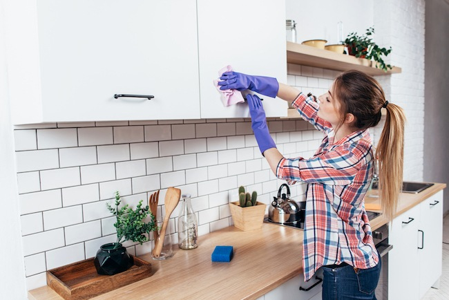 Woman cleaning her kitchen cabinets