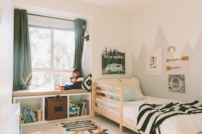 Little boy sitting on a bay window in his bedroom