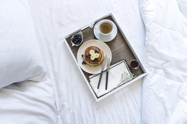 plate of blueberry pancakes on a bed with white sheets