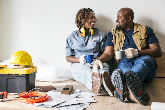 Couple sitting against the wall, holding hands in work clothes with home improvement items around them
