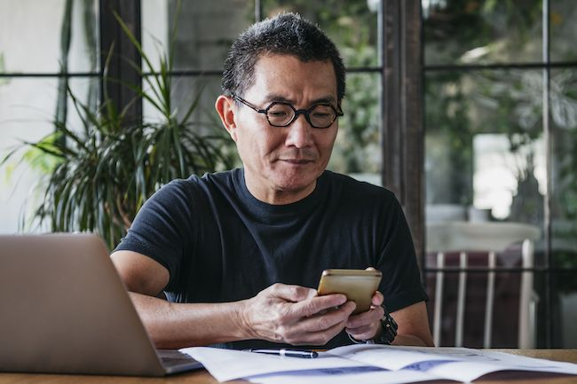 Mature man reading on his cell phone.