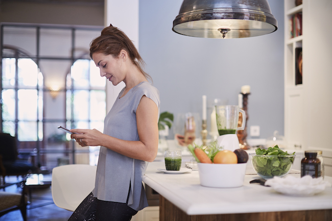 Woman relaxing with smartphone and a smoothie in the kitchen.