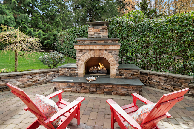 Outdoor fireplace with two Adirondack chairs.