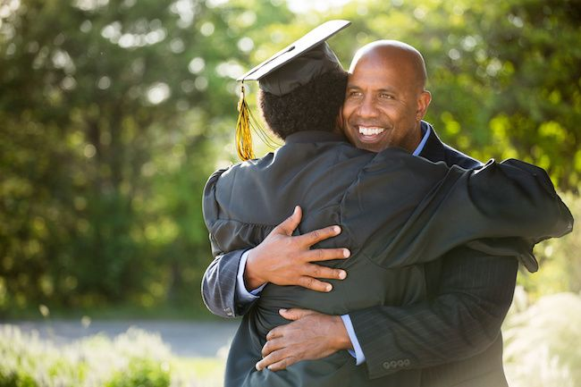 African American father and son hugging in graduation gown.