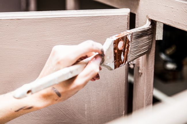 Close-up of a person painting their kitchen cabinet.