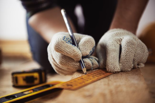 Photo of a carpenter's hands, measuring a piece of wood.