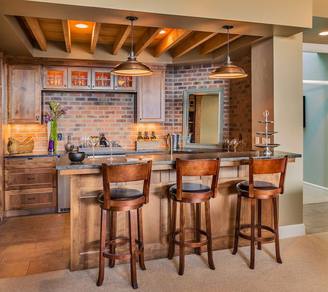 Eat-in bar and kitchen with exposed brick backsplash.