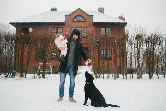 Young family with dog in front of house.