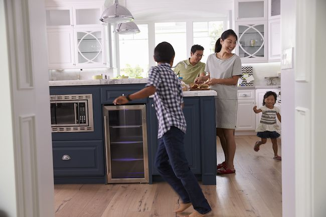 Family in kitchen, children running around.