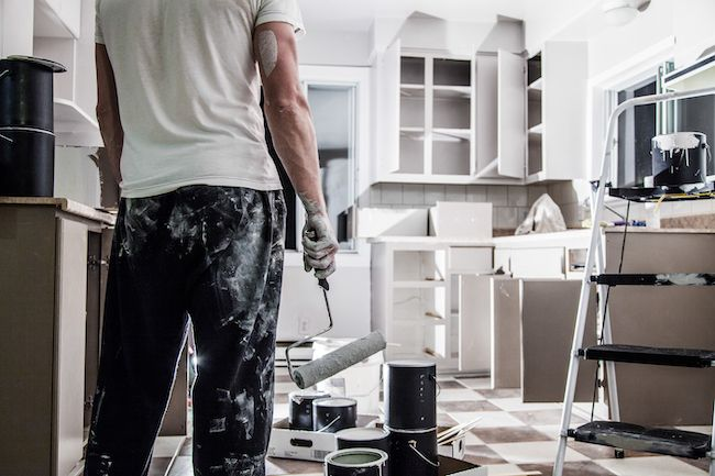 Man ready to tackle the project of painting his own kitchen cabinets.