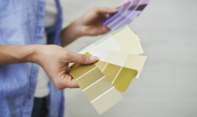 Paint swatches fanned out in a woman's hands. She is deciding what color to paint her kitchen cabinets.