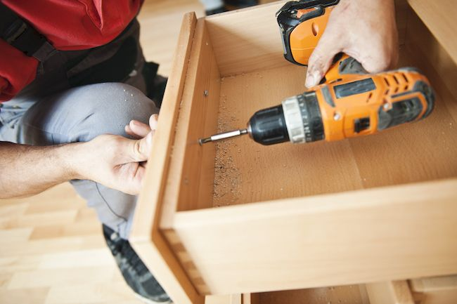 Person reassembling cabinets with drill.