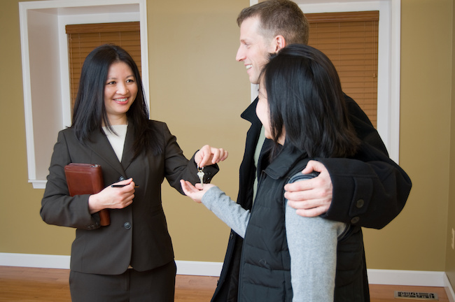 Woman Realtor offering key to house to couple.