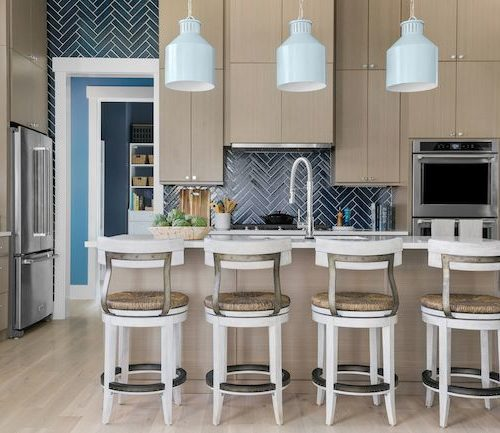 HGTV Dream Home 2020 - Kitchen Featuring Beige And White - Four White Hightop Chairs, Tiled Backsplash And Three Blue Pendant Lights