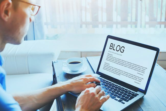 man wearing glasses and writing a blog about real estate
