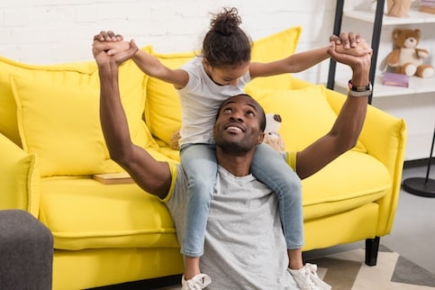 Father sitting on floor against a couch holding his daughter on his shoulders in living room