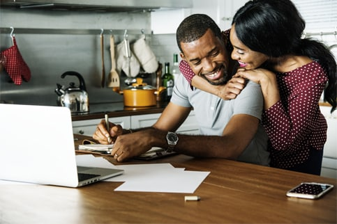 Couple Hugging in Kitchen Over Laptop