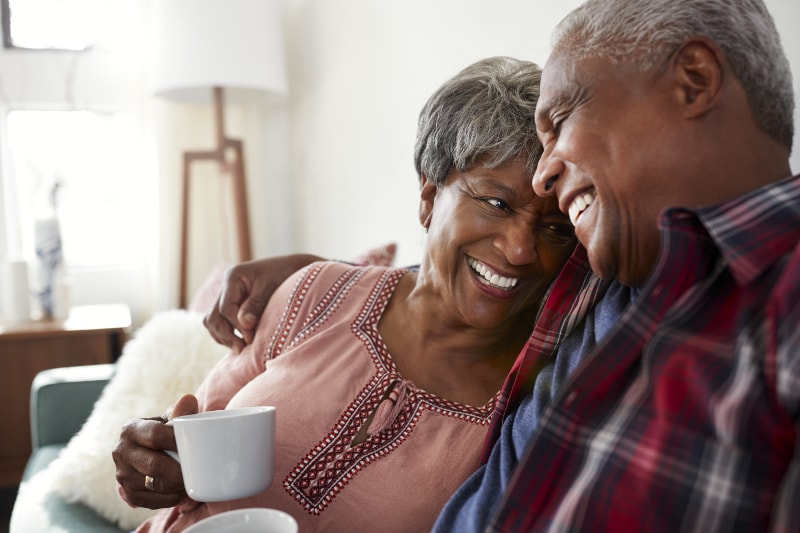 Older couple cuddling with coffee
