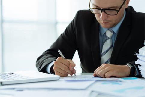 Man in suit signing hiring documents