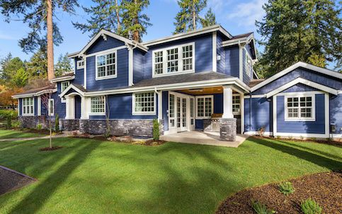 Large blue house with big yard.