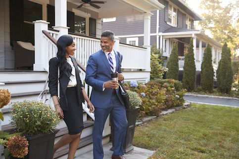 Couple in business attire leaving a house.