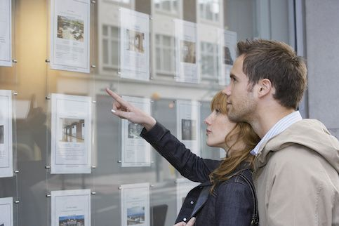 Young couple looking at real estate postings in a window.