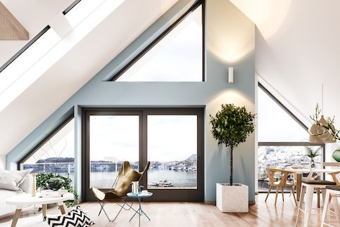 Scandinavian interior loft with large windows and sparse furniture.
